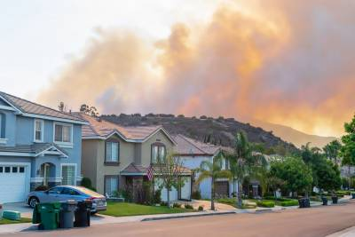 Fire burns behind houses without clear wildfire home protection