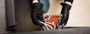 A man's gloved hand opening a safe for home valuables and removing family